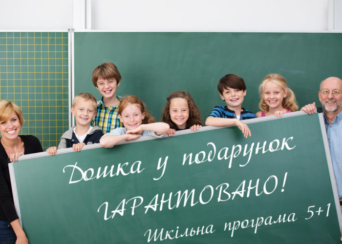 Happy school team of young students and teachers standing behind a large black chalkboard with copyspace smiling happily at the camera